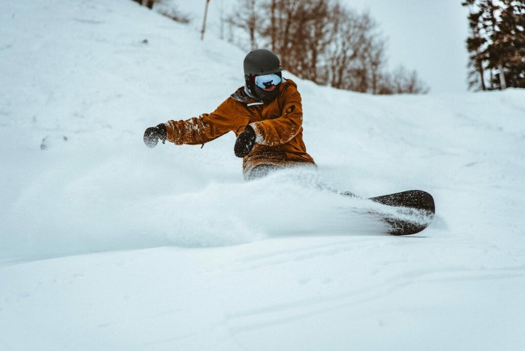 A picture showing a man snowboarding outside