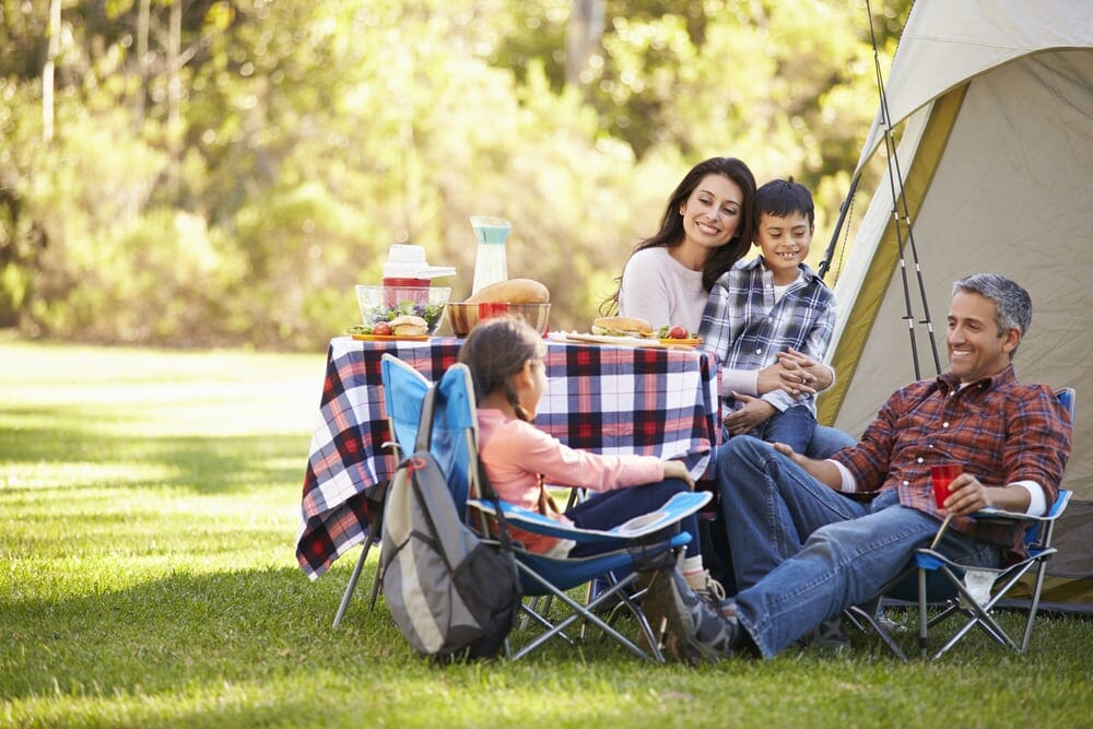 A picture showing a Family Enjoying Camping Holiday In Countryside